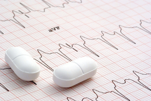 Heart pills on an EKG