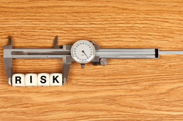 Scrabble pieces spelling out the word risk placed in a measure to detail measuring and managing risk