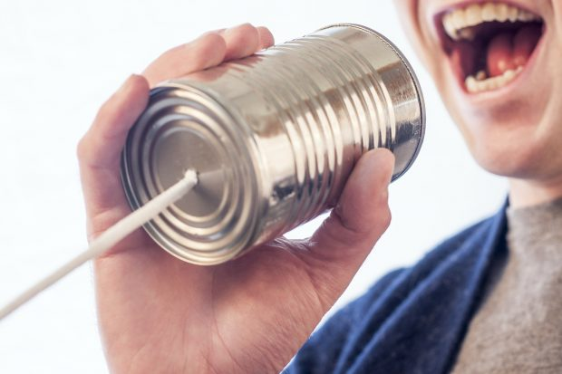 Individual speaking into a tin can acting as an acoustic speech-transmitting device.