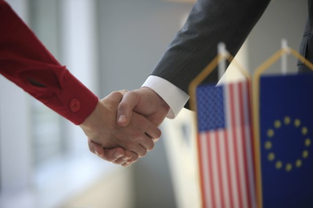 Handshake in front of Usa and Eu flags