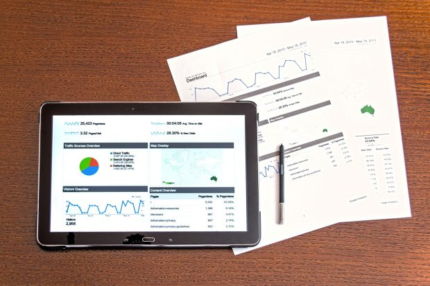 Tablet screen with a number of graphs displayed placed on top of papers