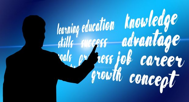 Person pointing to a board with the words: learning, education, sklls. success, growth, job, growth