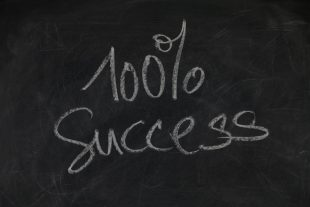 Blackboard with 100% success written on it