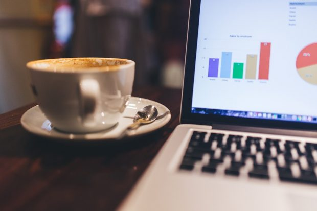 coffee cup next to open laptop displaying bar chart