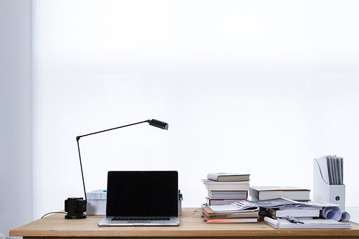 desk, on which is placed an open laptop, desk lamp, books and documents.