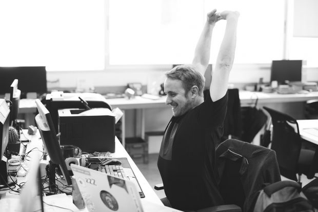 man in office, working on desktop PC, smiling, arms in the air, in expression of joy.