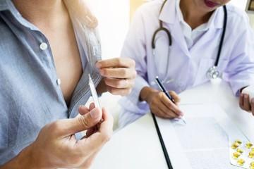 doctor, with patient, recording patient's medical details