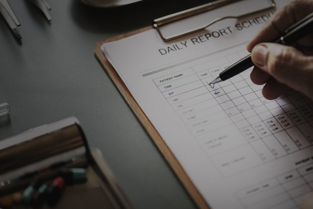 close-up of hand of medical professional completing a Patient Daily Report Schedule form