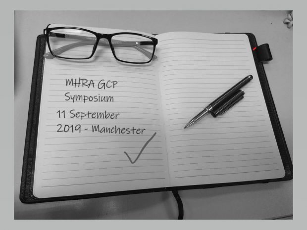 Open notebook. Written on the page is: MHRA GCP Symposium, 11 September 2019, Manchester