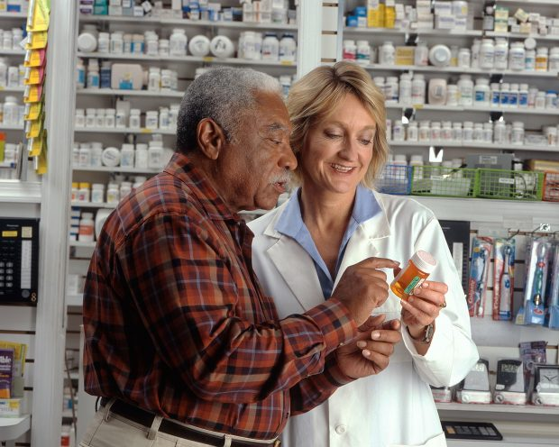 Gentleman consulting with a pharmacist about the medicine she is holding